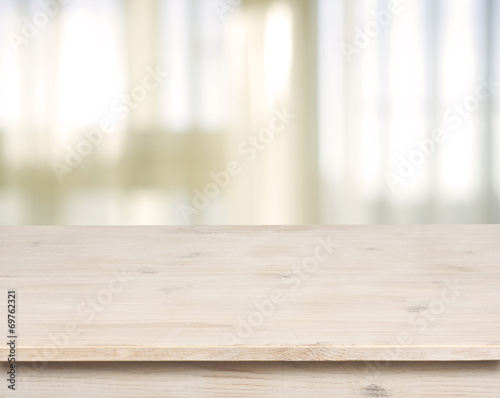 Leinwanddruck Bild Wooden table on defocuced window with curtain background