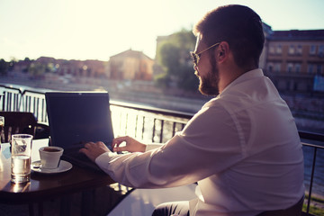 Businessman Sitting and Working on Laptop at Cafe