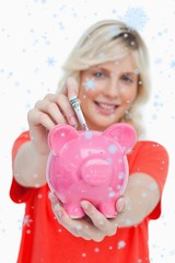 Young blonde woman putting notes into piggy bank