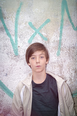 portrait of a teenager boy in front of a graffiti