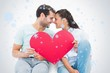 Composite image of cute couple sitting holding red heart