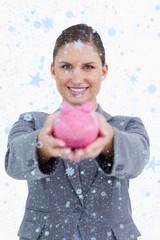 Composite image of smiling bank clerk offering piggy bank