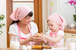 Mother and child prepare cookies at kitchen
