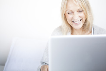 Mature woman using laptop in bedroom laughing