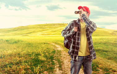 Male backpacker with binocular over green meadow background
