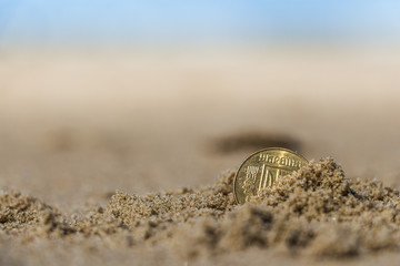 Business coins at holiday in the sand on the beach, North Sea