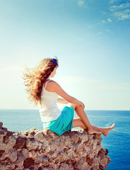 Young beautiful girl sits on a hill and looking at the sea