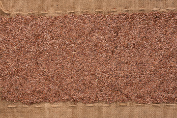 Flax seeds lying on sackcloth between the lines