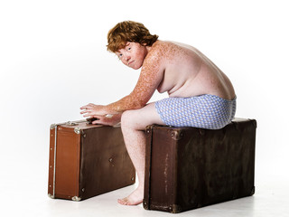 Undressed red-haired boy with old suitcases