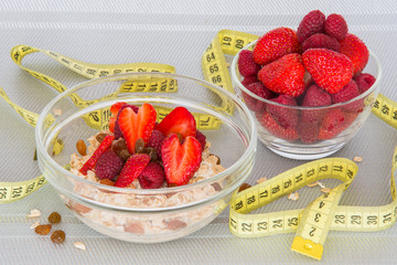 Oatmeal with fresh strawberries and berries with measuring tape.