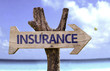 Insurance wooden sign with a beach on background