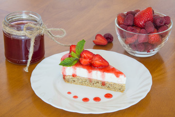 Strawberry cheesecake on a plate, berries and jam.
