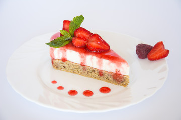 Strawberry cheesecake and berries on plate isolated.
