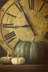 Still life of pumpkins and old clock