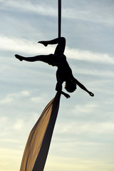 woman acrobatic dancer on aerial silk, aerial contortion