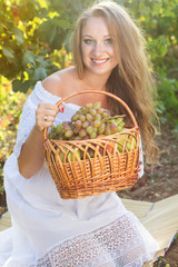 Portrait of young beautiful woman holding grapes