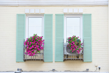 windows with wooden shutters decorated with pink flowers