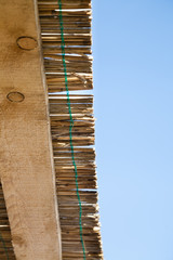Closeup of traditional reed and wooden roof with blue sky
