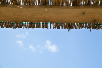horizontal traditional reed and wooden roof with blue sky