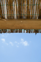 Vertical traditional reed and wooden roof with blue sky