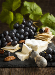 Delicious cheese crackers appetizer with grapes and pecans on co
