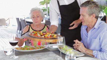 Waiter Serving Pizza To Senior Couple In Outdoor Restaurant
