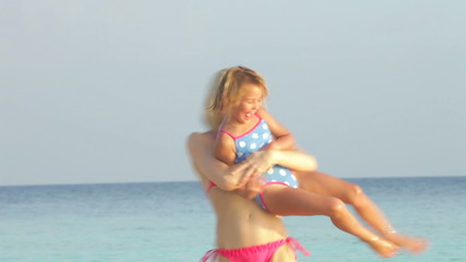 Mother And Daughter Having Fun In Sea On Beach Holiday