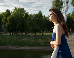 Pensive girl looks into the distance near river