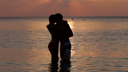 Silhouette Of Romantic Couple Kissing In Sea