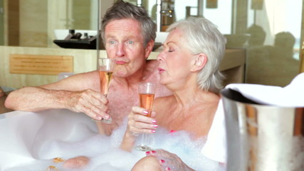 Senior Couple Relaxing In Bath Drinking Champagne