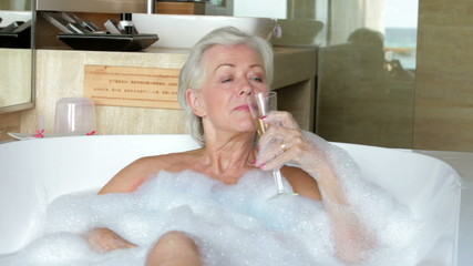 Senior Woman Relaxing In Bath Drinking Champagne
