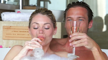 Couple Relaxing In Bath Drinking Champagne Together