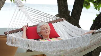 Senior Woman Relaxing In Beach Hammock
