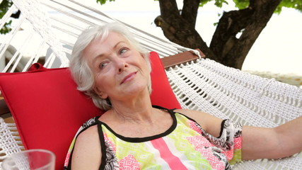 Senior Woman Relaxing In Beach Hammock With Champagne