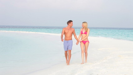 Romantic Couple Walking On Beautiful Tropical Beach