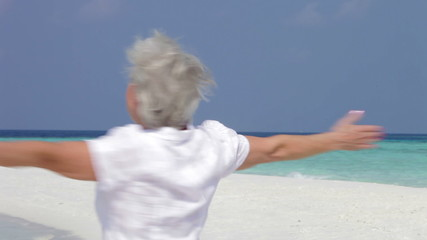 Senior Woman With Arms Outstretched On Beautiful Beach