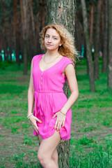 Slender girl in red dress near tree