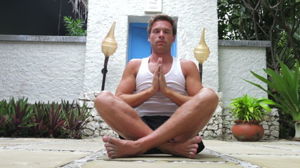 Man Doing Yoga Exercises Outdoors At Health Spa