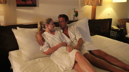 Couple Relaxing In Hotel Room Wearing Robes