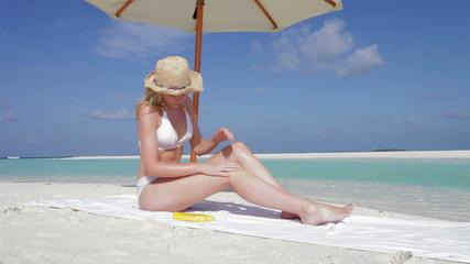 Woman Applying Sun Lotion On Beach Holiday
