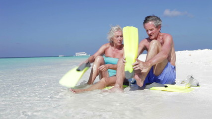 Senior Couple With Snorkels Enjoying Beach Holiday