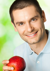Happy smiling man with apple, outdoors