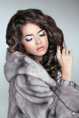 Beautiful brunette Fashion girl in Mink Fur Coat isolated on gra