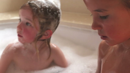 Parent Helping Girls To Wash Hair In Bath