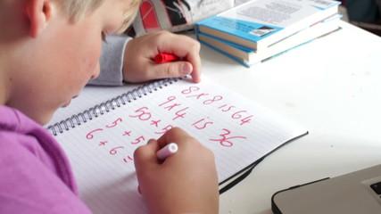 Boy Doing Math's Homework In Bedroom