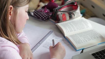 Girl Doing Written Homework In Bedroom