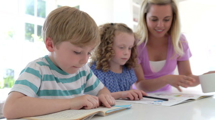 Mother Helping Children With Homework In Kitchen