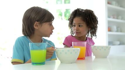 African American Children Having Breakfast In Kitchen