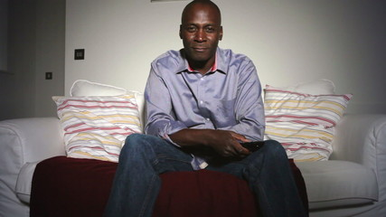 Mature African American Man On Sofa Watching TV