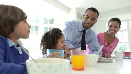 Family Having Breakfast Before Husband Goes To Work